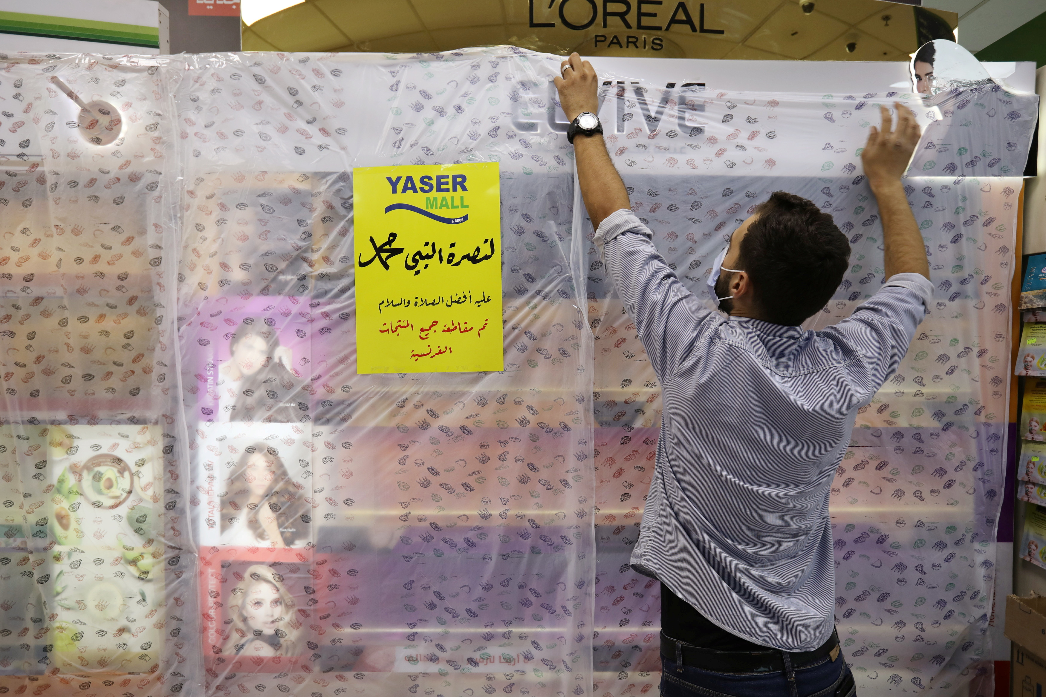 A worker of a mall covers French products in protest against French cartoons of the Prophet Mohammad in Amman